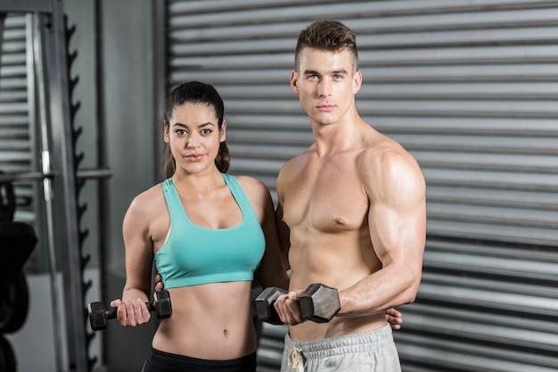 Apto casal levantando halteres e olhando para a câmera no ginásio Foto Premium