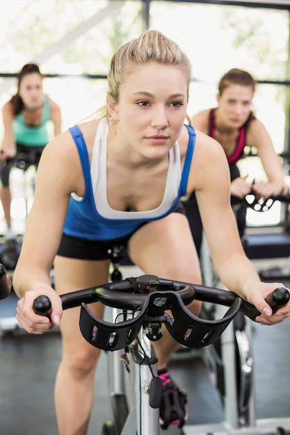 Apto grupo de pessoas usando bicicleta ergométrica juntos no ginásio Foto Premium