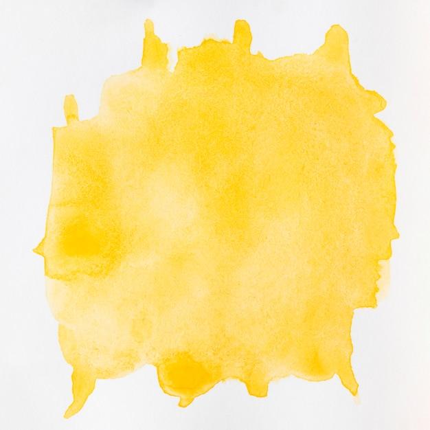 Aquarela líquido amarelo espirra sobre fundo branco Foto gratuita
