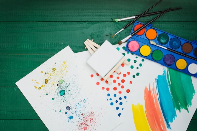 Aquarela manchada e pincelada em folha branca com mini cavalete e paleta de aquarela Foto gratuita