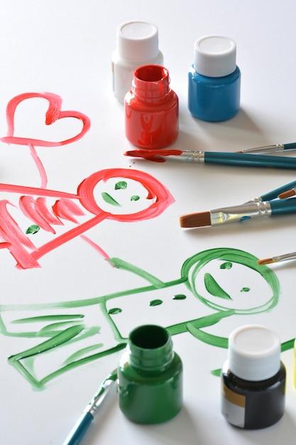 Aquarelas e pincéis com desenhos de crianças em tela branca Foto Premium