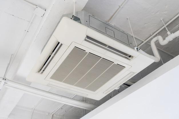 Ar condicionado tipo cassete com instalação de sistema de iluminação e proteção contra incêndio no teto. Foto Premium