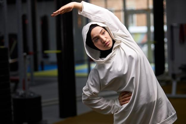 Árabe fitness feminino faz flexões laterais no centro de fitness, prepara o corpo antes de treinar no equiomento esportivo, aquece o corpo e os músculos Foto Premium