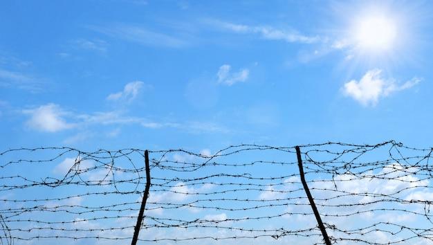 Arame farpado no conceito do fundo, da liberdade, da prisão e da esperança do céu azul. Foto Premium