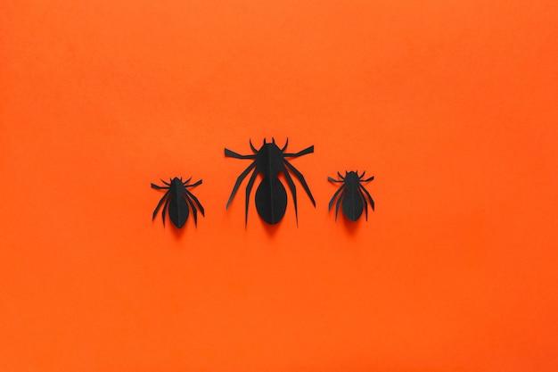 Aranhas de papel em um fundo laranja Foto Premium