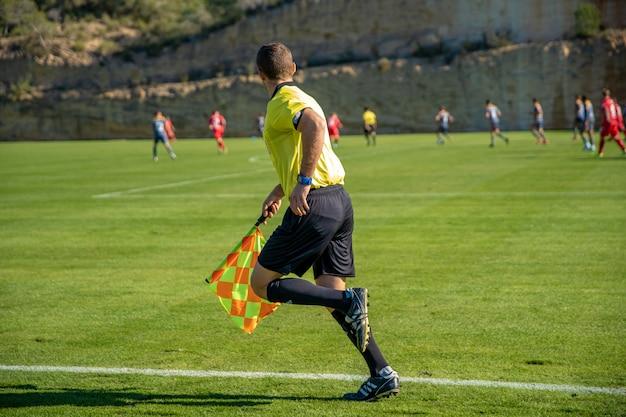 Árbitro assistente em uma partida de futebol assistindo o jogo Foto Premium