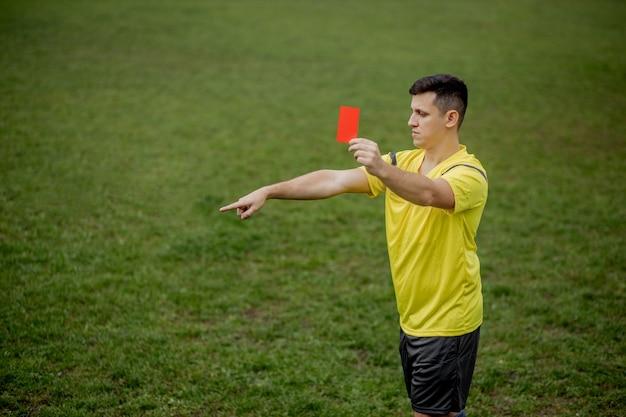 Árbitro de futebol com raiva mostrando um cartão vermelho e apontando com a mão no pênalti. Foto Premium