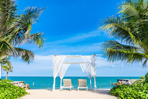 Arco branco e espreguiçadeiras na praia tropical Foto gratuita