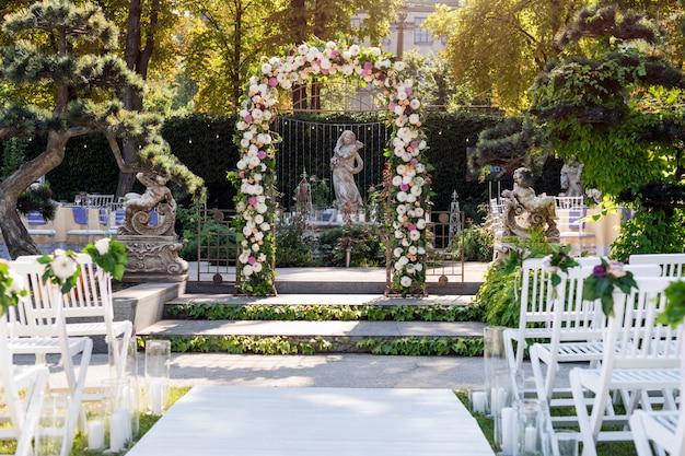 Arco de casamento com flores ao ar livre. cerimônia de casamento no jardim com esculturas e fonte. Foto Premium