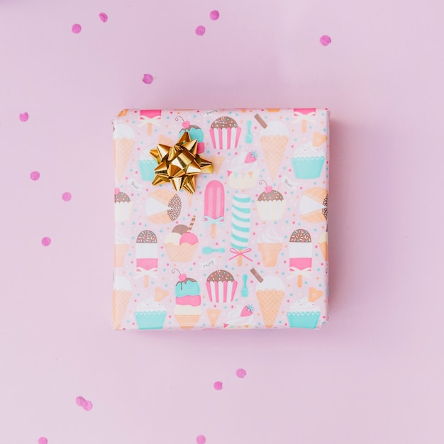 Arco dourado na caixa de presente embrulhado sobre o fundo rosa Foto gratuita