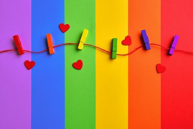 Arco-íris colorido prendedores de roupa de madeira e corações vermelhos no fundo da bandeira de arco-íris Foto Premium