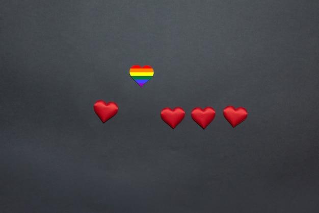 Arco-íris e corações vermelhos em um fundo amarelo, em uma vista superior e em um espaço para o texto. escolhendo um parceiro de amor Foto Premium