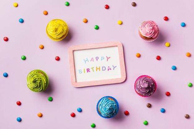 Ardósia de feliz aniversário rodeada de gemas coloridas e muffins em fundo rosa Foto gratuita