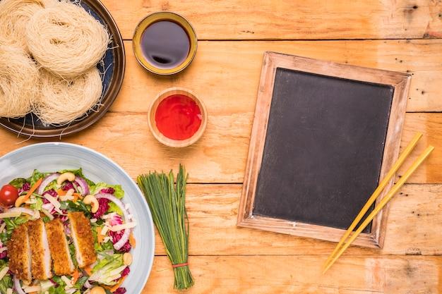Ardósia em branco com pauzinhos e comida tradicional tailandesa na mesa de madeira Foto gratuita