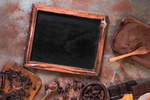 Ardósia em branco de madeira com barra de chocolate, cacau e pó na mesa rústica Foto gratuita