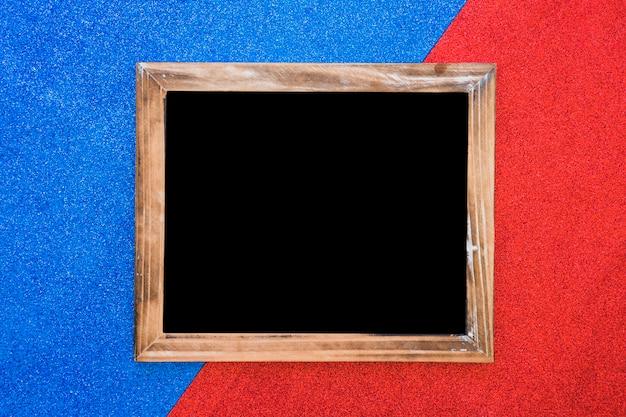 Ardósia em branco de madeira em pano de fundo duplo azul e vermelho Foto gratuita