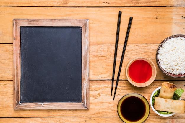 Ardósia em branco perto dos pauzinhos; rolinho primavera; arroz e molhos na mesa de madeira Foto gratuita