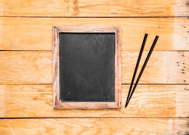 Ardósia preta em branco com pauzinhos na prancha de madeira Foto gratuita