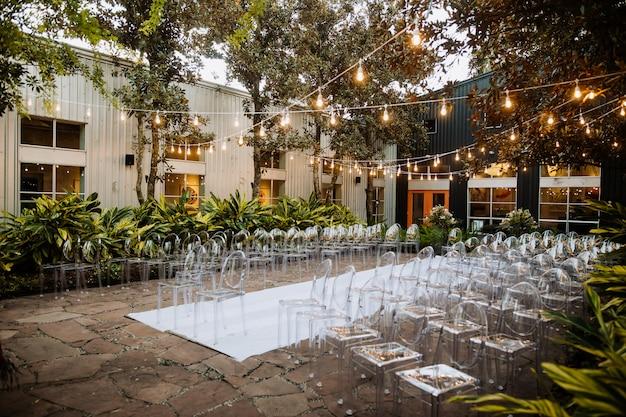 Área cerimonial decorada ao ar livre, com cadeiras transparentes modernas e um lindo enfeite com muitas árvores e plantas Foto gratuita