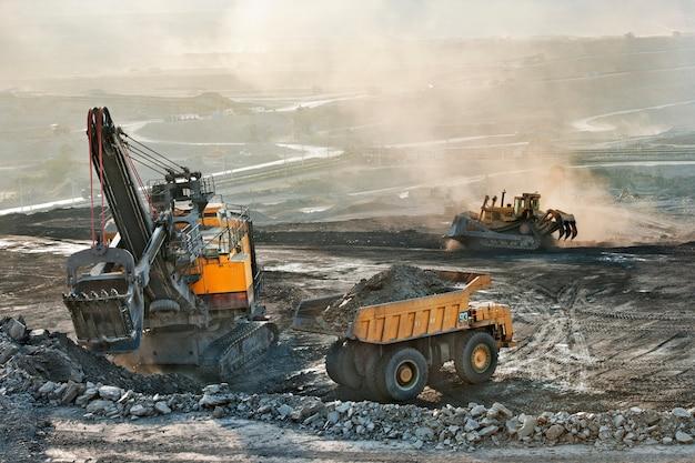 Área de mina de carvão muitos caminhão pesado e máquina escavadora para a indústria de mineração Foto Premium