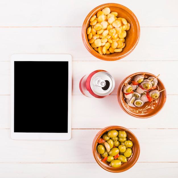 Área de trabalho de cozinha com lanches e tablet Foto gratuita