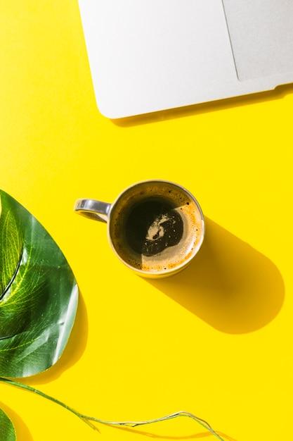 Área de trabalho de escritório com uma xícara de café e biscoitos Foto gratuita