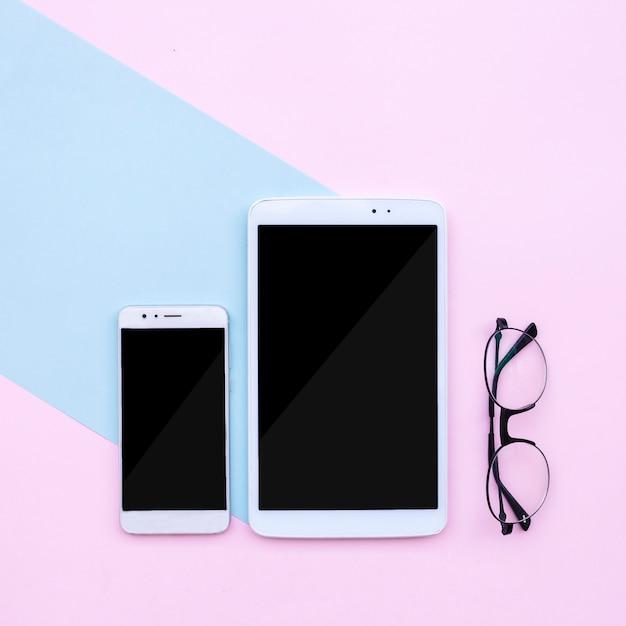 Área de trabalho moderna com telefone e tablet e óculos na luz azul e fundo rosa Foto gratuita