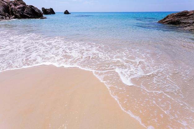 Areia branca da praia tropical bonita do mar com a onda que deixa de funcionar na costa arenosa Foto Premium