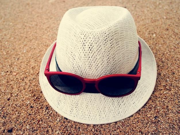 Areia da praia dos óculos de sol do chapéu relaxa férias Foto gratuita