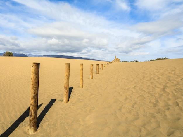 Areia nas dunas de maspalomas, um pequeno deserto em gran canaria. areia e céu, e uma cerca de madeira marcando a área proibida da reserva natural de pássaros la charca. Foto Premium
