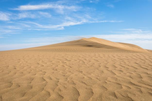 Areia nas dunas de maspalomas, um pequeno deserto em gran canaria, espanha. areia e céu. Foto Premium
