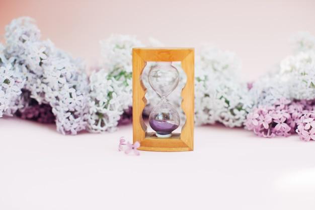 Areia que corre através dos bulbos de uma ampulheta que mede o tempo de passagem em uma contagem regressiva a um fim do prazo, em um fundo lilás da mola da flor com espaço da cópia. Foto Premium