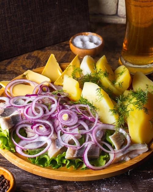 Arenque com batatas cozidas manteiga cebola vermelha endro sal e copo de cerveja Foto gratuita