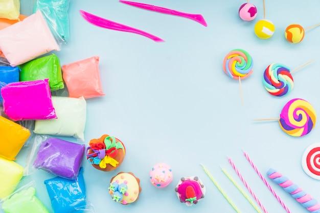 Argila colorida em saco de plástico com bolo falso e pirulito em fundo azul Foto gratuita