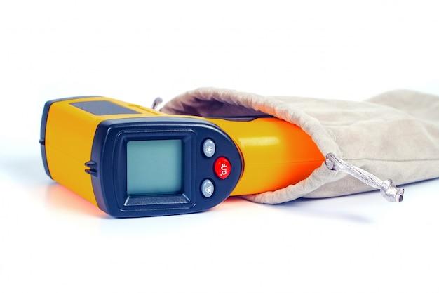 Arma amarela do termômetro infravermelho usada para medir a temperatura no branco. Foto Premium
