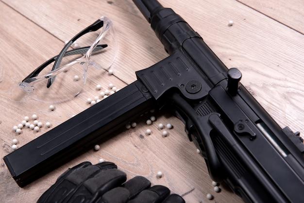 Arma de airsoft com óculos de proteção e muitas balas Foto Premium