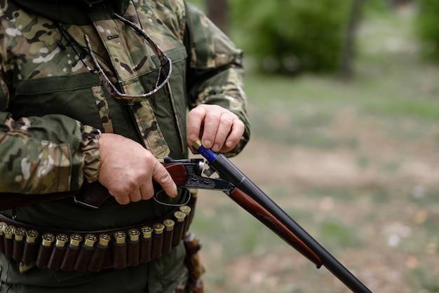 Arma de carregamento de caçador profissional com cartucho. Foto Premium