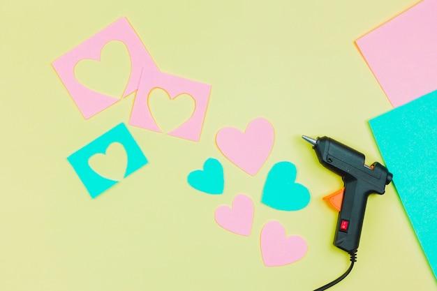 Arma de cola e cortar a forma de coração azul e rosa de papel em fundo amarelo Foto gratuita