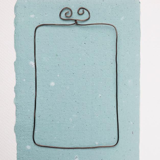 Armação de arame retangular em papel azul contra o pano de fundo branco Foto gratuita