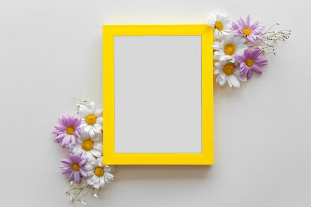Armação de borda amarela decorada com flores bonitas contra a superfície branca Foto gratuita