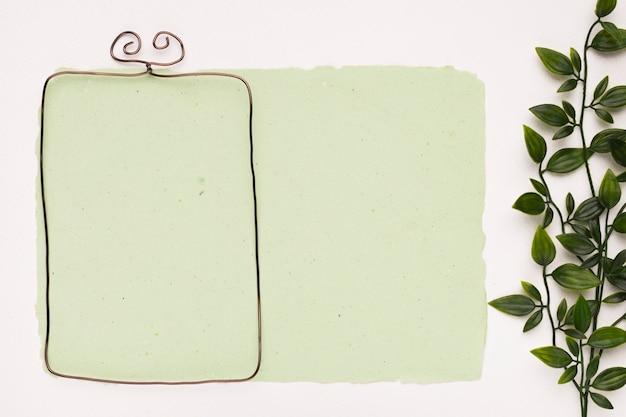 Armação de borda metálica em papel verde hortelã perto das folhas no pano de fundo branco Foto gratuita