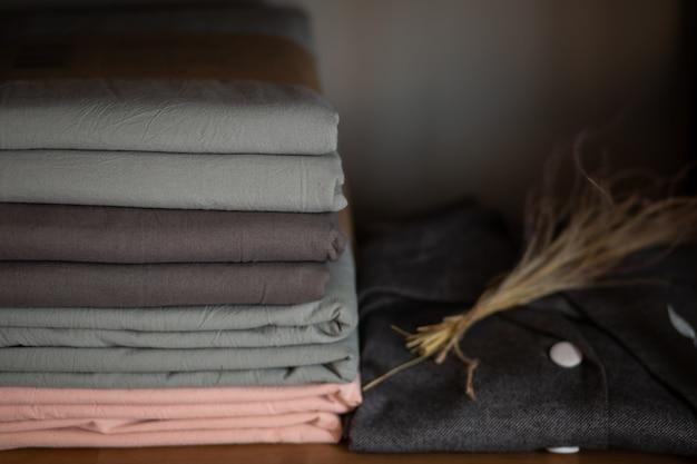 Armário de madeira com roupa de cama e roupas em casa ou em uma loja, conceito de design no interior Foto Premium