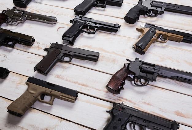 Armas de fogo. arma de fogo. o close up a arma encontra-se em um fundo branco de madeira. Foto Premium