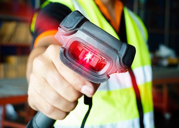 Armazene a mão do trabalhador que guarda o varredor do código de barras com varredura do laser vermelho. gerenciamento de estoque do armazém. Foto Premium