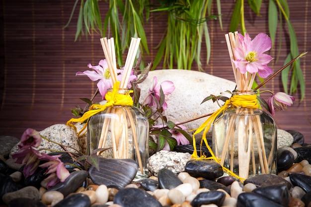 Aromaterapia, spa, tratamento de beleza e bem-estar com massagem com pedras, flores, frasco Foto Premium