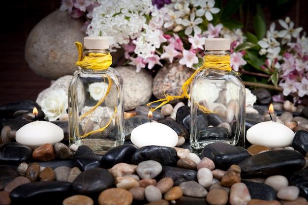Aromaterapia, spa, tratamento de beleza e bem-estar com pedras de massagem, flores, velas acesas Foto Premium