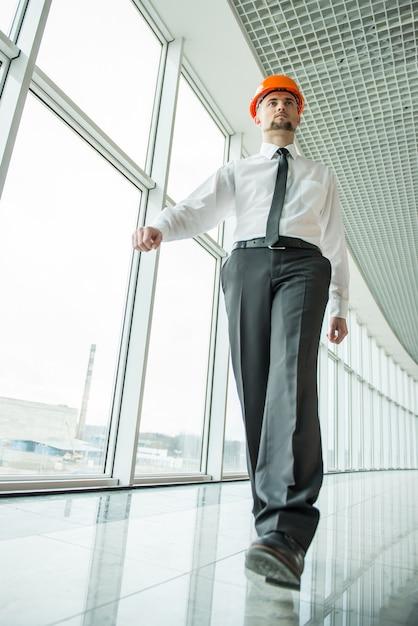Arquiteto confiante com capacete está andando no escritório. Foto Premium