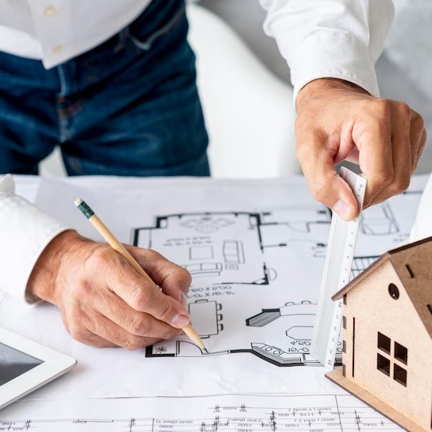 Arquiteto de alto ângulo, trabalhando em planos de construção Foto gratuita