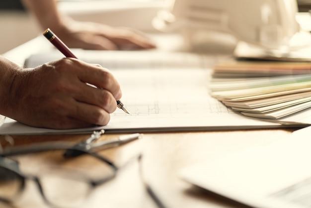 Arquiteto e engenheiro trabalhando documento de desenho sobre o planejamento do projeto e o andamento do cronograma de trabalho. Foto Premium