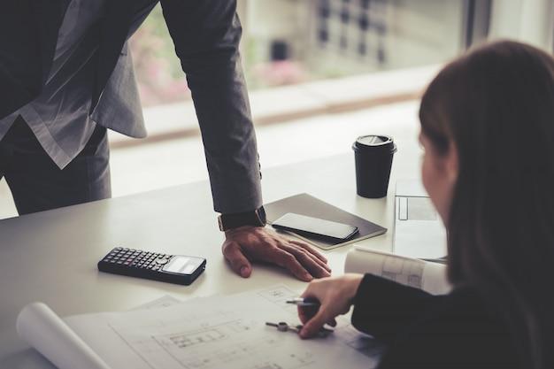 Arquiteto feminino está mostrando seu chefe o plano de construção de imóveis Foto Premium